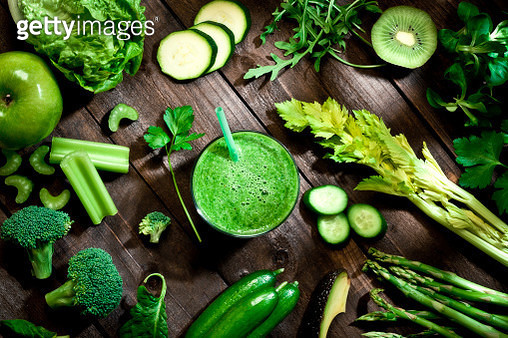 Top view of a rustic wooden table filled with green fruits and vegetables for a perfect detox diet. At the center of the frame is a glass with fresh green smoothie and a large variety of fruits and vegetables are all around it. Soft focus technique used.  - gettyimageskorea