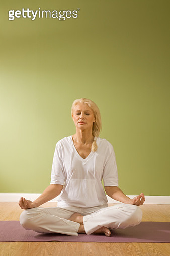 Mature Woman in lotus Yoga position, eyes closed - gettyimageskorea