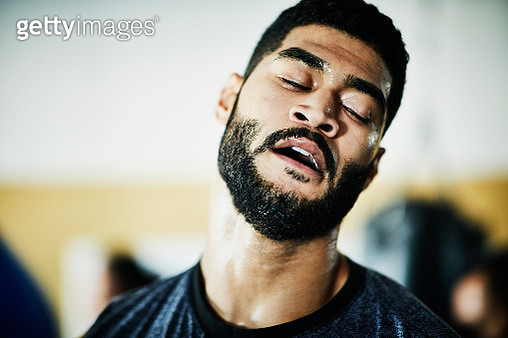 Portrait of sweating male boxer with eyes closed training in boxing gym - gettyimageskorea