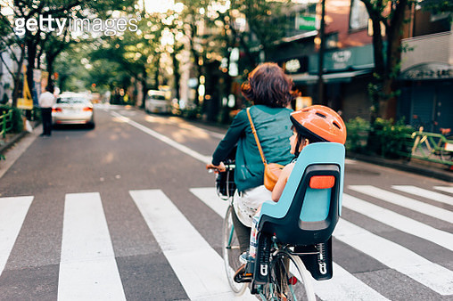 Mother cycling home with her child in urban city, Tokyo - gettyimageskorea
