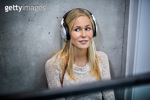 Young woman wearing headphones listening to music at concrete wall - gettyimageskorea
