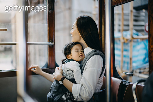 Young Asian mother with sleeping little daughter enjoying city scene through window while riding on city tram - gettyimageskorea