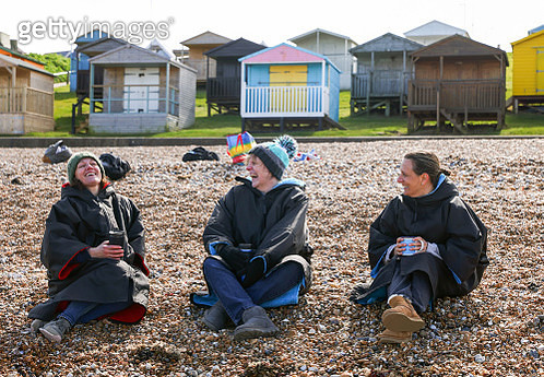 Group of friends sit and laugh on the beach - gettyimageskorea