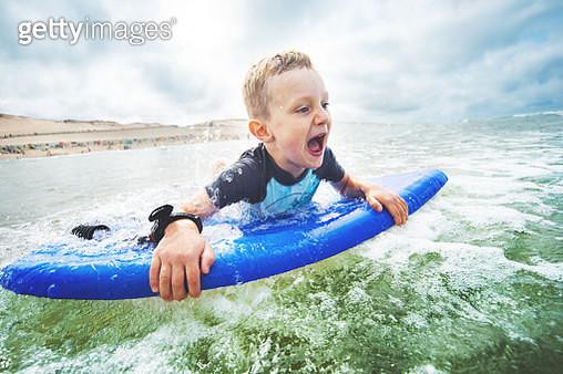 Little boy bodyboarding at the sea - gettyimageskorea