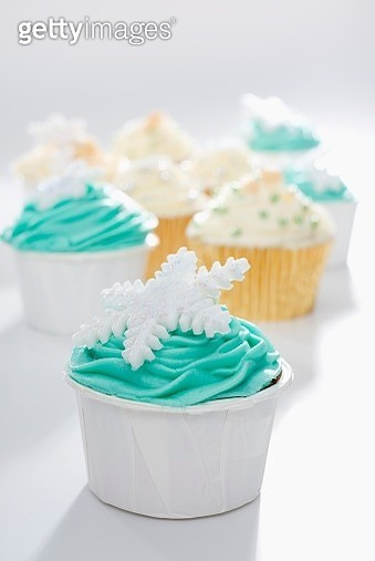 Cupcakes decorated with green and yellow frosting and snowflakes - gettyimageskorea