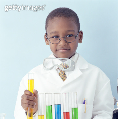 Boy (5-7) in white coat holding test tube, smiling, portrait - gettyimageskorea