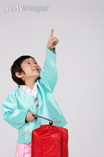 Boy (4-5) wearing hanbok and holding cheongsachorong lantern, pointing - gettyimageskorea