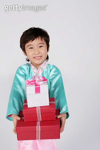 Portrait of boy (4-5) wearing hanbok and holding gifts, smiling - gettyimageskorea