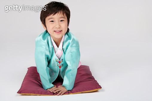Portrait of boy (4-5) wearing hanbok, lying on cushion, close-up, smiling - gettyimageskorea