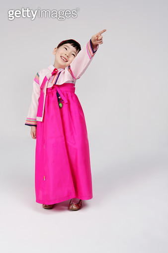 Girl (4-5) wearing hanbok and pointing, smiling - gettyimageskorea