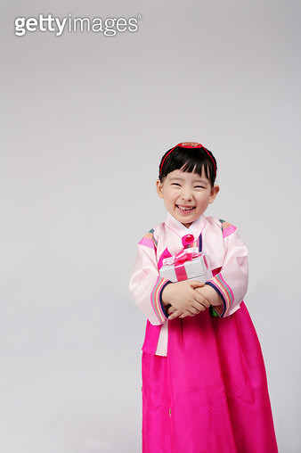 Portrait of girl (4-5) wearing hanbok and holding gift, smiling - gettyimageskorea