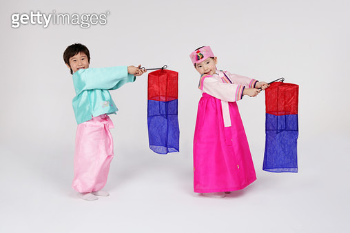 Portrait of girl and boy (4-5) wearing hanbok and holding cheongsachorong lantern, smiling - gettyimageskorea