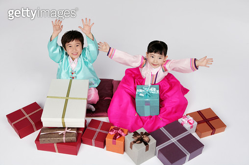 Portrait of girl and boy (4-5) in hanbok, holding gift boxes, elevated view - gettyimageskorea