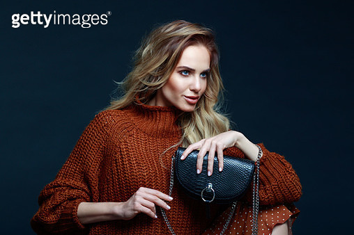 Portrait of long hair blond young woman wearing brown sweater and skirt, holding black purse, looking away. Studio shot against black background. - gettyimageskorea