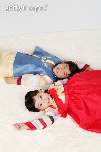 Portrait of girl and boy (4-5) in hanbok and lying on floor, smiling - gettyimageskorea