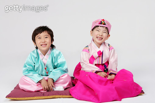 Portrait of girl and boy (4-5) wearing hanbok and sitting on cushion, smiling - gettyimageskorea