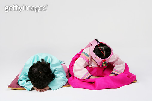 Girl and boy (4-5) wearing hanbok and sitting on cushion, - gettyimageskorea