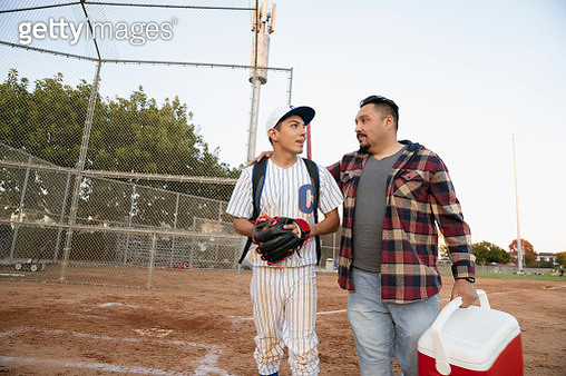 Latinx father and baseball player son walking off field - gettyimageskorea