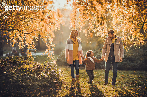 Happy parents taking a walk with their little daughter in autumn. - gettyimageskorea