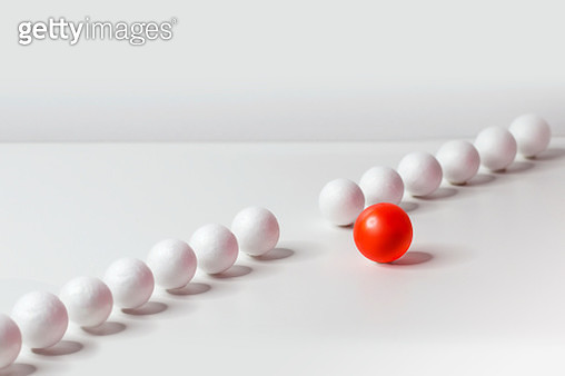 One red sphere venture out from a row of spheres. - gettyimageskorea