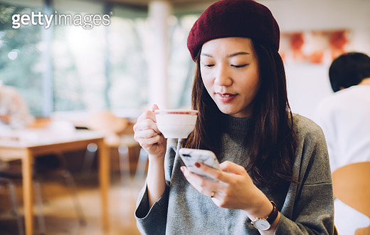Young woman drinking a cup of coffee and text messaging on mobile phone - gettyimageskorea