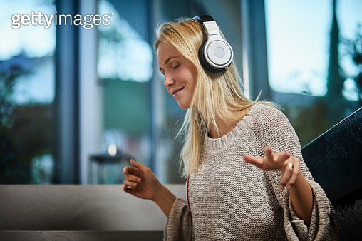 Young woman wearing headphones listening to music at home - gettyimageskorea
