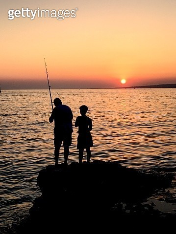 Silhouette Man With Son Fishing At Beach Against Sky During Sunset - gettyimageskorea