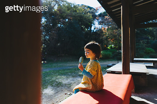 Portrait of a mixed race little girl eating ice cream bar - gettyimageskorea
