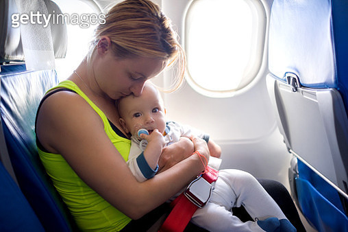 Young loving mother and her baby traveling by airplane. - gettyimageskorea