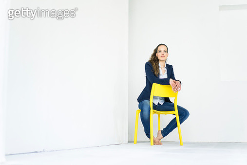 Businesswoman sitting on a yellow chair thinking - gettyimageskorea