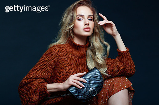 Portrait of long hair blond young woman wearing brown sweater and skirt, holding black purse, looking at camera. Studio shot against black background. - gettyimageskorea