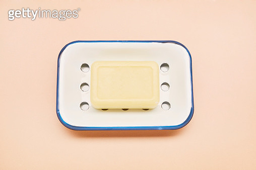 High angle view of an enamel soap dish and bar soap for washing hands on beige colored background - gettyimageskorea