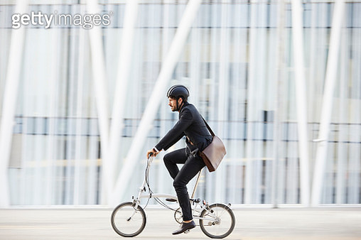 Businessman cycling on street by modern building - gettyimageskorea