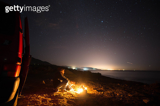 Man Sitting By Campfire On Mountain Against Sky At Night - gettyimageskorea