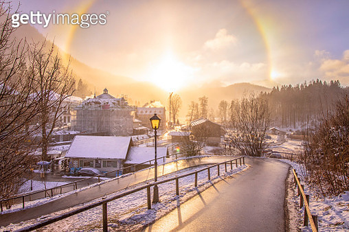Sun behind a lamp creating a rainbow in a European Snow scene - gettyimageskorea
