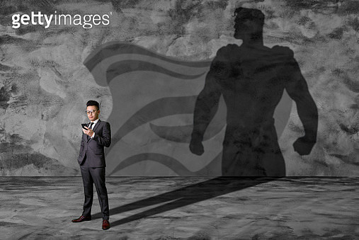 the abstract image of the businessman standing and overlay with his superhero shadow. - gettyimageskorea