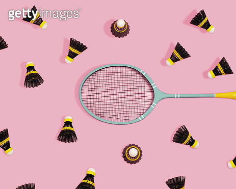 Black and yellow badminton birdies with racket on a pink background. - gettyimageskorea