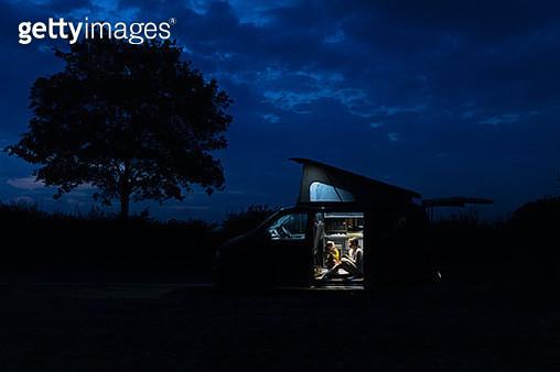 Woman talks to her daughter in their campervan at night - gettyimageskorea