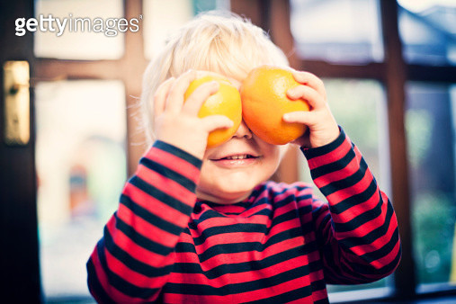 Child holding up oranges. - gettyimageskorea