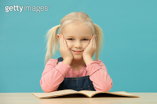 Studio portrait of a 4 year old blonde girl on a blue background - gettyimageskorea