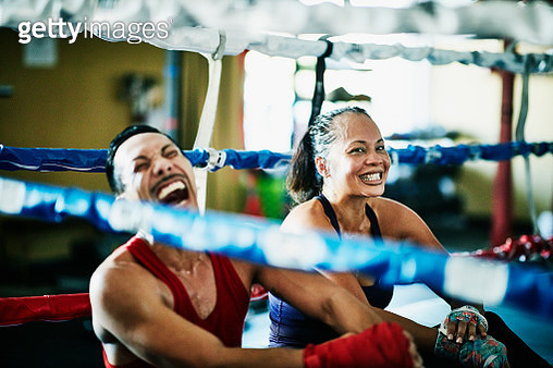 Laughing boxers sitting in boxing ring after training session - gettyimageskorea
