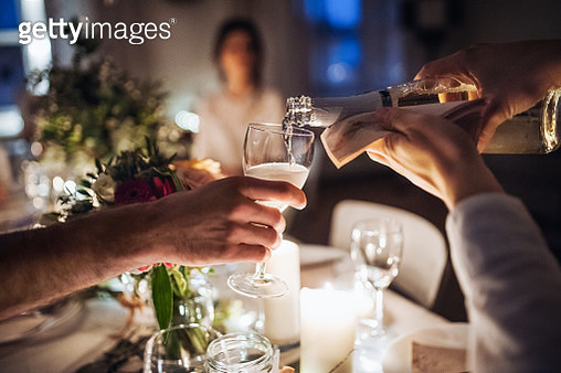 A Midsection Of Waiter Pouring Champagne Into A Glass On An Indoor Party At Night - gettyimageskorea
