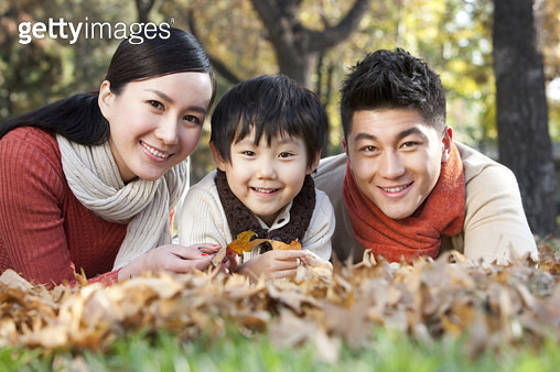 Young family lying on the grass surrounded by Autumn leaves - gettyimageskorea