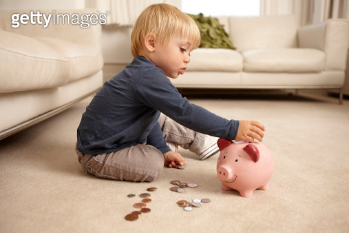 Boy putting coins in piggy bank - gettyimageskorea