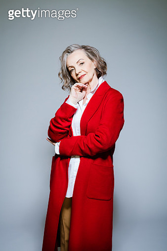 Elderly lady wearing red coat and white shirt standing with hand on chin against grey background, smiling at camera. Studio shot of female designer. - gettyimageskorea