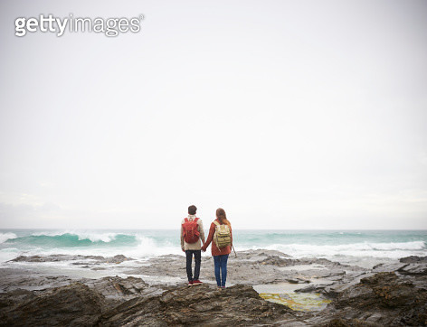 Couple holding hands and looking out to sea. - gettyimageskorea