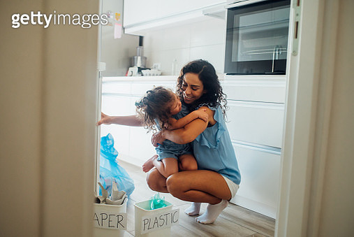 Mother and daughter hugging when recycling - gettyimageskorea