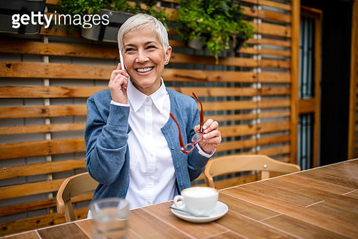 Smiling mature woman talking on the mobile phone. - gettyimageskorea