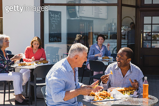 Senior male friends enjoying fish and chips outside cafe - gettyimageskorea