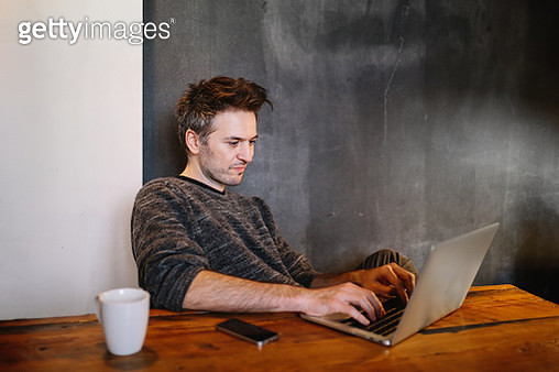 Young man finishing work at home on his laptop - gettyimageskorea